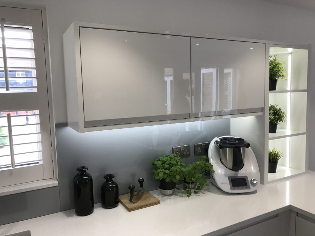 Corner image of white, shiny kitchen surfaces with creative lighting. Some storage facilities on the side of the cabinet.
