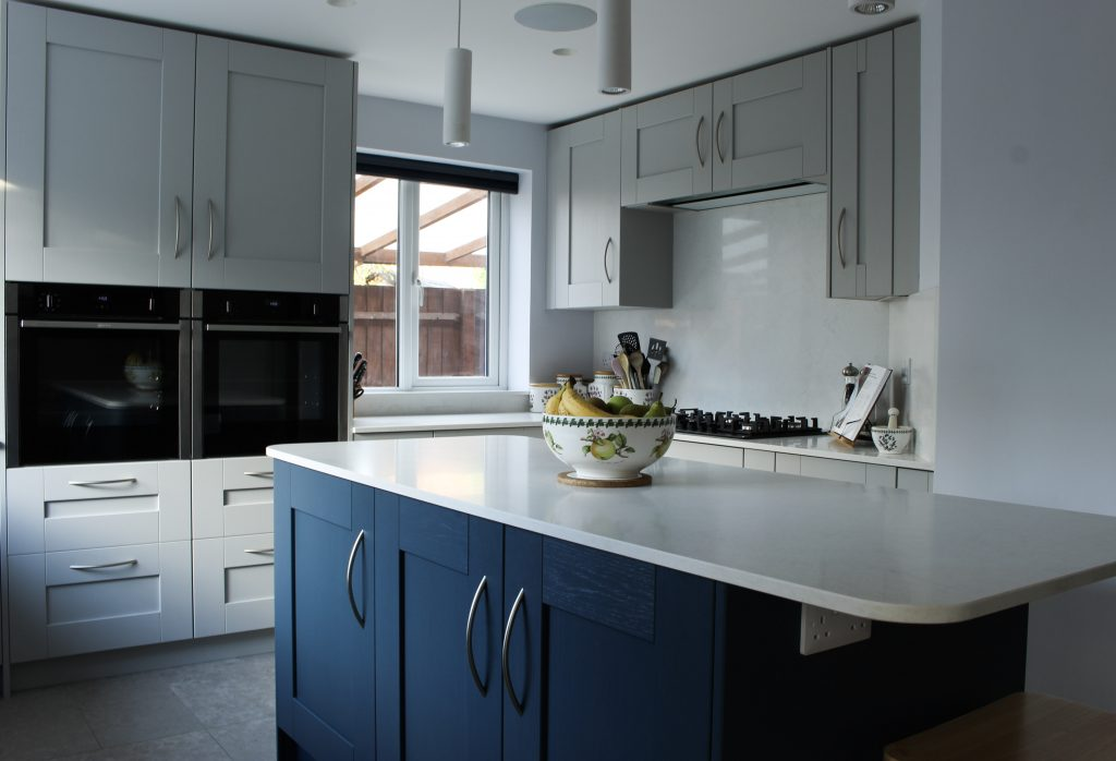 A large kitchen island with a dark blue feature colour. U-shaped kitchen surrounding the island with Quartz worktops.